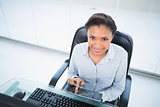 Cheerful young dark haired businesswoman using a tablet pc