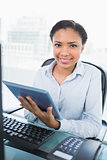 Smiling young dark haired businesswoman using a tablet pc