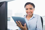 Joyful young dark haired businesswoman using a tablet pc