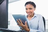 Amused young dark haired businesswoman using a tablet pc