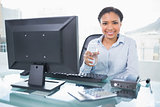 Pleased young dark haired businesswoman holding a glass of water