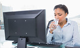 Relaxed young dark haired businesswoman drinking water