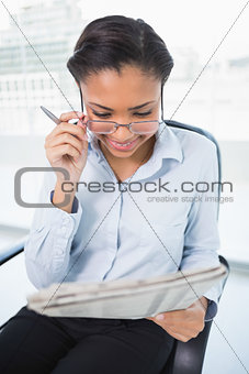 Charming young dark haired businesswoman reading a newspaper