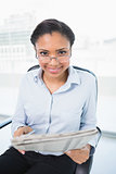Attractive young dark haired businesswoman reading a newspaper