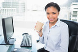 Pleased young dark haired businesswoman holding a cup of coffee