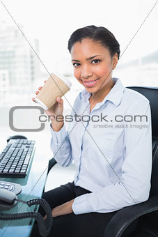 Amused young dark haired businesswoman drinking coffee