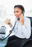 Thinking young dark haired businesswoman answering the telephone while holding a cup of coffee