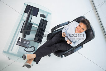 Beautiful young dark haired businesswoman filing her nails sitting at her desk