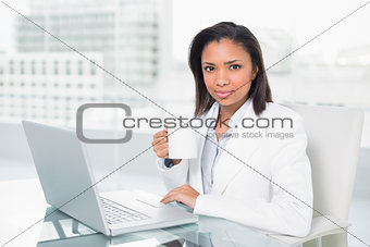 Calm young dark haired businesswoman using a laptop