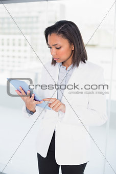 Thoughtful young dark haired businesswoman looking at her tablet pc