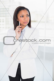 Attractive young dark haired businesswoman posing looking away