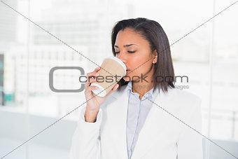 Cute young dark haired businesswoman enjoying coffee
