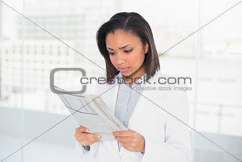 Focused young dark haired businesswoman reading a document