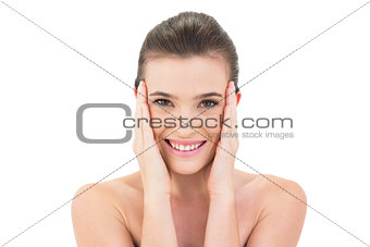 Happy woman touching her face and looking at camera