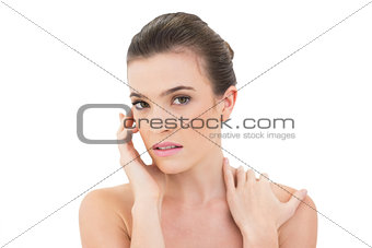 Attractive woman holding hand on face and shoulder