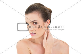 Serious woman touching her neck while looking at camera