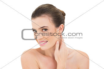 Smiling woman touching her neck while looking at camera