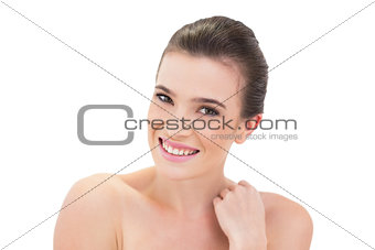 Cheerful natural brown haired model touching her shoulder