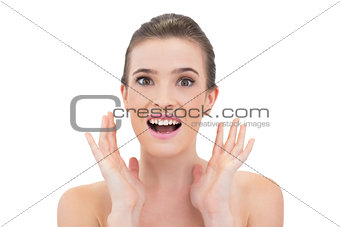 Amazed natural brown haired model raising her hands