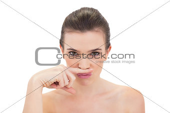 Pouting natural brown haired model putting her finger under her nose