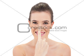 Amused natural brown haired model touching her nose