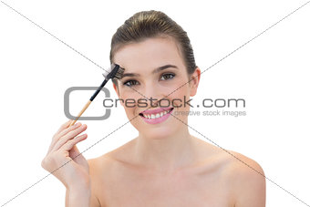 Amused natural brown haired model using an eyebrow brush