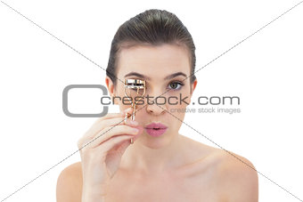 Pouting natural brown haired model using an eyelash curler