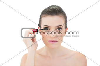 Focused natural brown haired model applying mascara