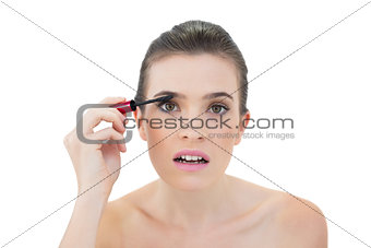 Attentive natural brown haired model applying mascara