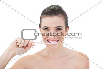 Pretty natural brown haired model brushing her teeth