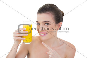 Amused natural brown haired model showing her glass of orange juice