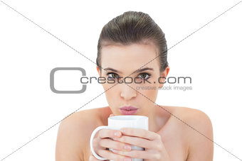 Charming natural brown haired model blowing on her coffee