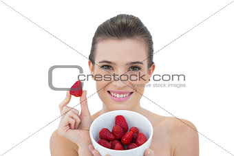 Beautiful natural brown haired model showing a bowl of strawberries