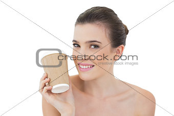 Amused natural brown haired model holding a cup of coffee