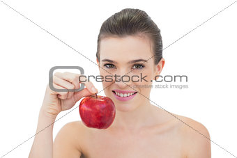 Beautiful natural brown haired model holding an apple