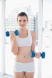 Motivated fit brown haired model in sportswear exercising with dumbbells