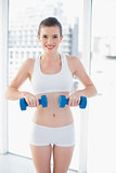 Smiling fit brown haired model in sportswear exercising with dumbbells
