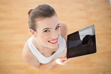 Delighted fit brown haired model in sportswear holding a tablet pc
