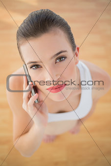 Serious fit brown haired model in sportswear making a phone call