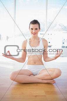 Smiling fit brown haired model in sportswear meditating in lotus position