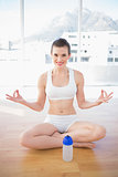 Happy fit brown haired model in sportswear meditating in lotus position