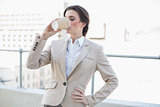 Peaceful stylish brown haired businesswoman drinking coffee