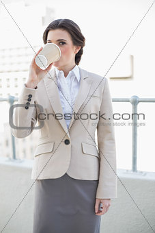 Calm stylish brown haired businesswoman drinking coffee