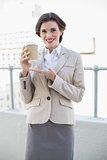 Delighted stylish brown haired businesswoman showing her coffee