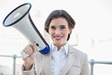 Pleased stylish brown haired businesswoman holding a megaphone