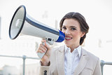 Pretty stylish brown haired businesswoman holding a megaphone