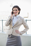 Cheerful stylish brown haired businesswoman calling with her mobile phone