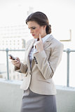 Troubled stylish brown haired businesswoman looking at her mobile phone