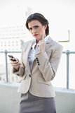Frowning stylish brown haired businesswoman holding a mobile phone