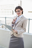 Content stylish brown haired businesswoman holding a notebook and a pen